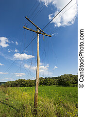 Old unnecessary wooden electrics pylon with broken wires