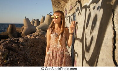 girl walking along graffiti wall near sea at sunset HD