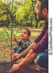 Giving a new life. Cheerful little boy helping his father to...