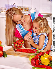 Child feed mother at kitchen - Happy child feed mother at...