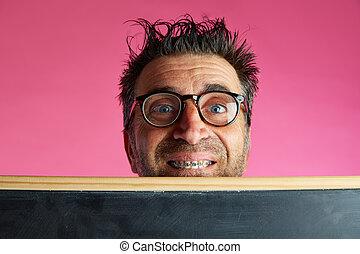 Nerd man crazy behind blackboard funny gesture