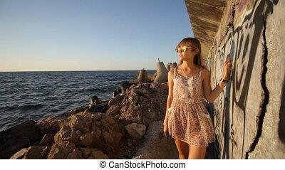 girl walking along graffiti wall near sea at sunset