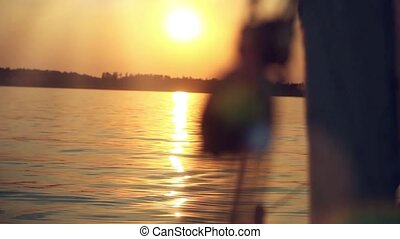sailing into the sunset on blurred reflected water with...