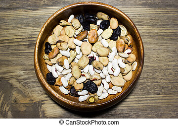 full bowl of different haricot beans on the wooden table