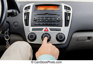 close up of male hand using climate control in car