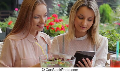 Lunch in a cozy cafe. Girls using tablet laughing.