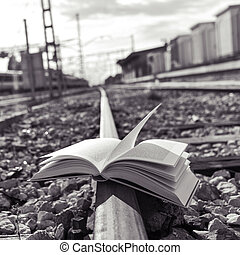 book on the railroad tracks, black and white - closeup of an...
