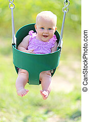 Happy Baby Girl Swinging at Playground - A happy little 6...