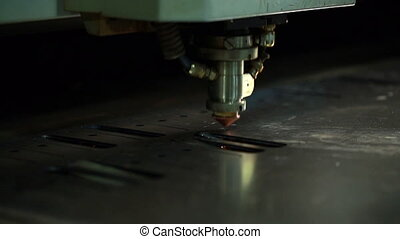 Machine makes hole in metal sheet by laser head - View of...