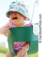 Baby Girl Crying in Toddler Swing - A baby girl is crying as...