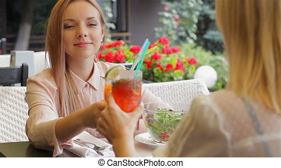 Girlfriends drinking cocktails and talking. Women on the...