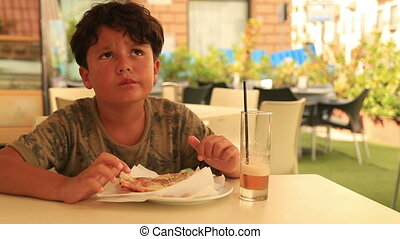 Cute boy eating pizza at the restaurant