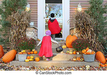 Children in Cape Costumes Trick-or-Treating on Halloween -...