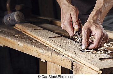 carpenter hands working with a chisel and carving tools -...