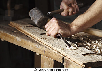 carpenter hands working with a chisel and hammer - Closeup...