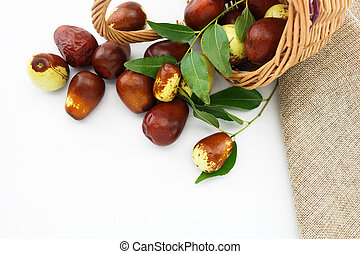 Jujube fruits in wicker basket closeup, on white background