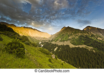 sunset above mountain peaks with forest on hills