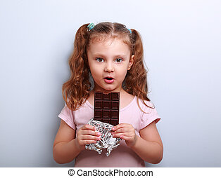 Fun expression kid girl eating dark chocolate and looking...