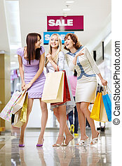 Girl-friends in shop - Three young women with bags laugh in...