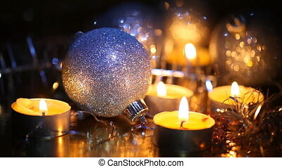 Burning small candles and Christmas tree decorations against...