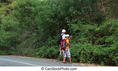 Father and son walking in nature and eating blackberry