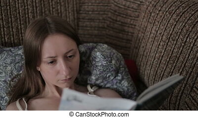 Young woman reading a book on the couch