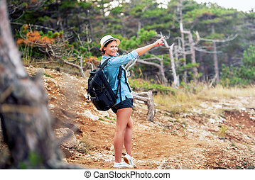 female with backpack trekking on mountains, walking through forest and hills. Happy woman, ready for adventure exploring the nature