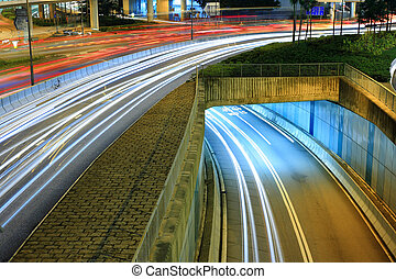Highway in city at night with trails of car lights