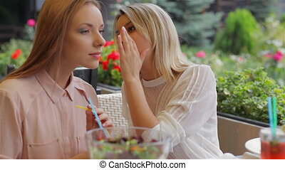 Girls whispering in the cafe. Two girls friends relaxing...