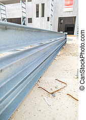 Steel girders in outdoor warehouse.