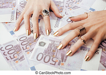 hands of rich woman with golden manicure and many jewelry...