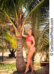 blond girl in bikini leans on palm smooths shaken by wind...