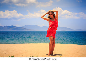 blond girl in red stands on sand beach lifts hands over her...