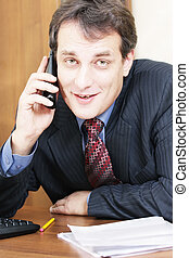 Smiling businessman at desk with phone