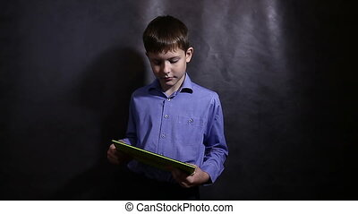 Teenage boy in a blue shirt playing running on the tablet dark background video