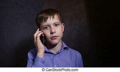 Teenage boy in a blue shirt calls on a mobile phone dark background video