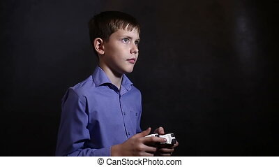 Teenage boy in a blue shirt, playing a video game console...