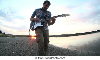 man musician outdoors at sunset near the lake plays the...
