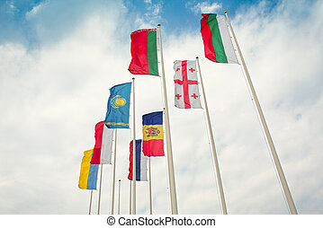 Row of european and asian flags against blue sky background