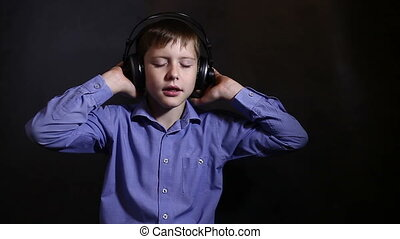 Teenage boy in a blue shirt in big headphones listening to music closed eyes dark background video