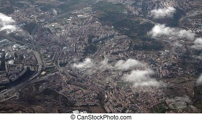 The Airplane is Flying Above the City and Clouds, view from...