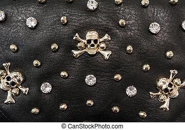 Black leather texture with metal skulls.