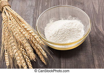 Flour and wheat ears on wooden table
