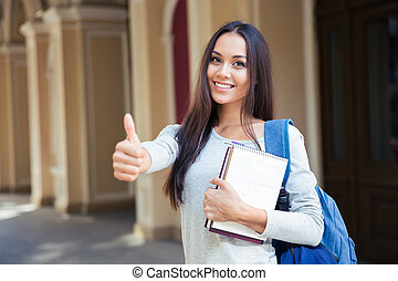 Smiling female student showing thumb up - Portrait of a...