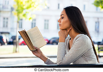 Woman reading book on the bench outdoors - Portrait of a...