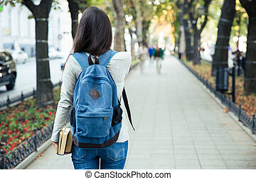 Back view portrait of a female student walking in the city...