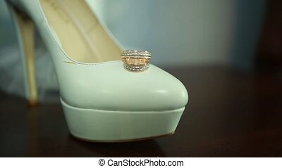 Wedding rings are on the brides shoes