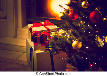 Toned photo of Christmas tree and gift boxes against burning fireplace