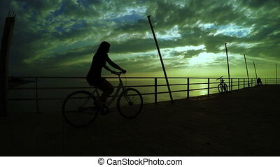 Girl on Bicycles at sunset sea - Sunset on sea and standing...