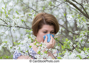 Woman with allergic rhinitis in spring garden - Woman with...